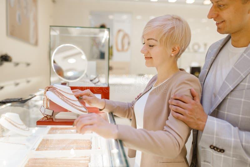 Miłości para wybiera złoto łańcuch w sklepie jubilerskim fotografia royalty free
