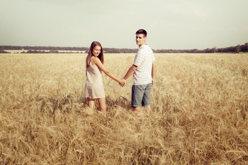 Miłości pary odprowadzenie w śródpolnych mienie rękach zdjęcia stock