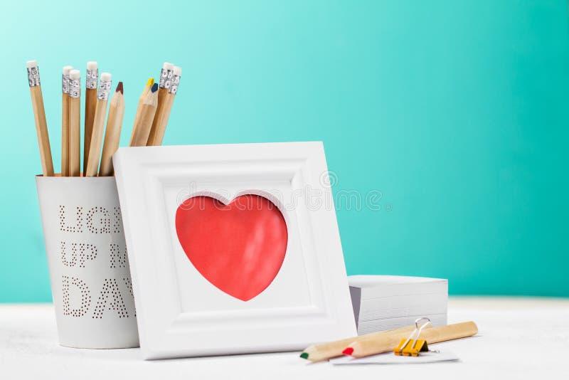 Miłości pojęcie z fotografii ramą, ołówkami i czerwonym sercem, horyzontalny zdjęcia stock