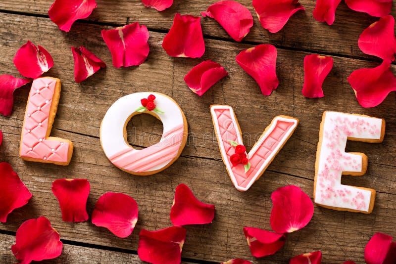 Miłości słowo z czerwonymi płatkami fotografia stock