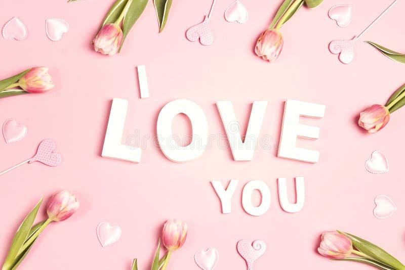 Miłości wyznanie z tulipanami kwitnie na różowym pastelowym tle fotografia stock