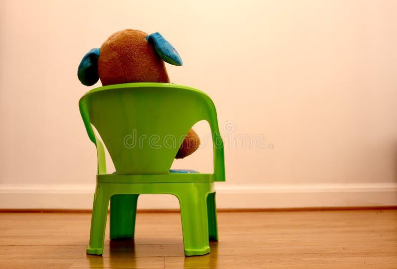 Miś siedzi na krześle patrzeje pustą biel ścianę zdjęcia stock