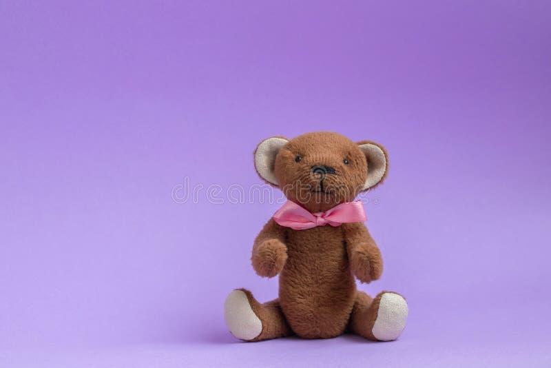 Miś siedzi na purpurowym tle Miś zabawka z menchia łękiem Odbitkowa przestrze?, poczt?wka Mokiet zabawka jest handmade fotografia royalty free