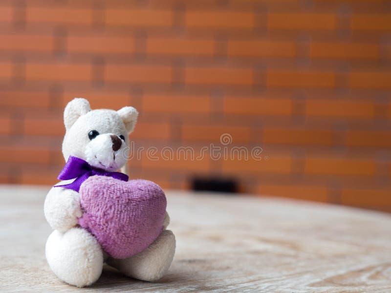Miś trzyma purpurowe serce Umieszczający na drewnianym biurku obrazy stock