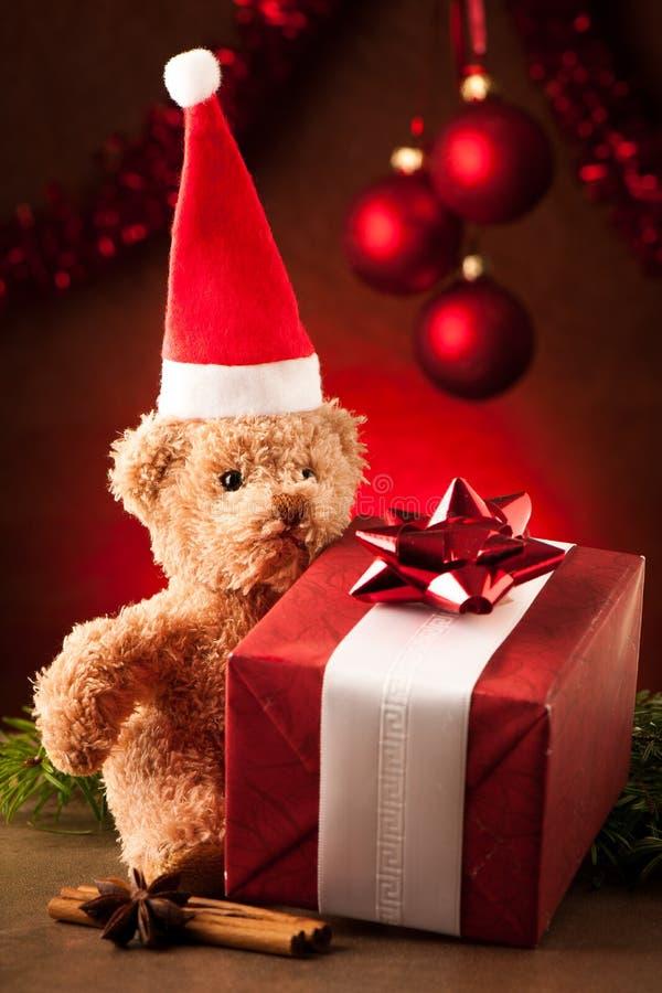 Miś z czerwonym Santa Claus kapeluszem i boże narodzenie teraźniejszość obraz stock