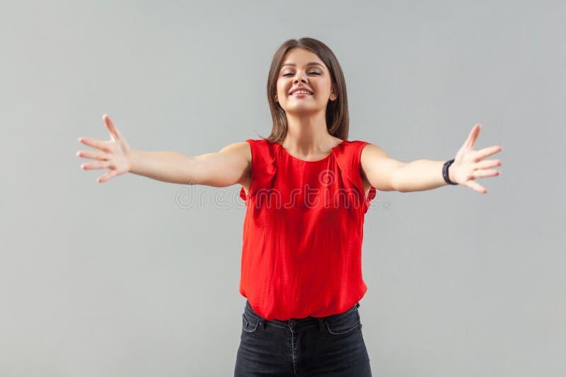 Mi abbracci! Ritratto di una ragazza felice, bellissima, in camicia rossa, con braccia alzate, sorriso di denti e denti. immagine stock libera da diritti