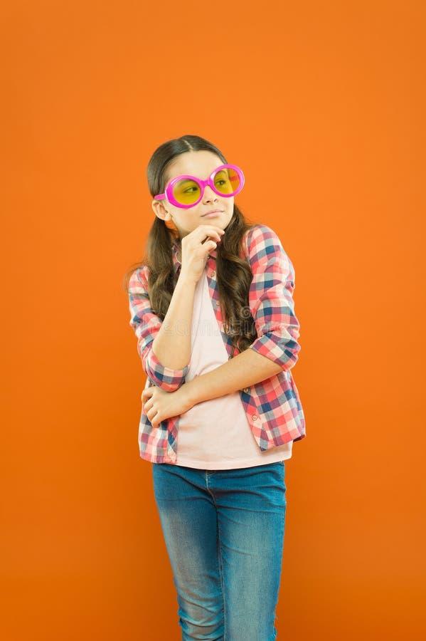 Mi accesorio preferido Pequeño niño que piensa en accesorio de lujo del partido en fondo anaranjado Ojo que lleva de la muchacha  imagen de archivo libre de regalías
