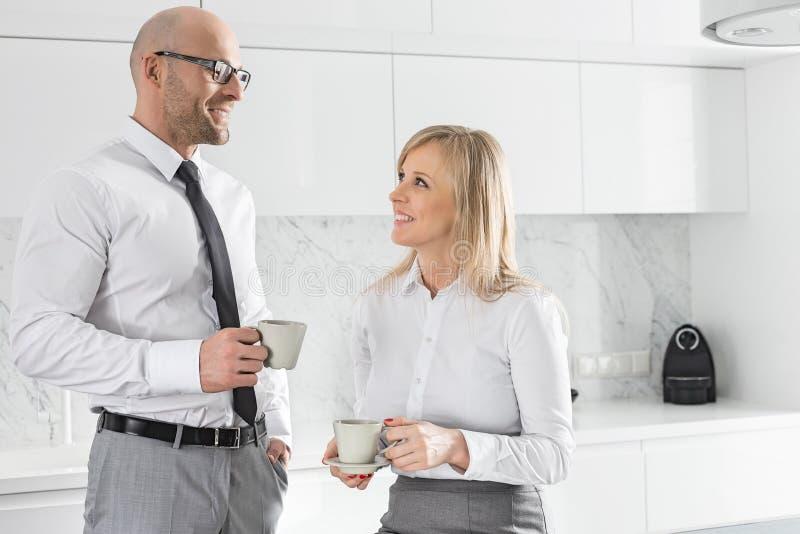 Mi couples adultes heureux d'affaires ayant le café dans la cuisine image libre de droits