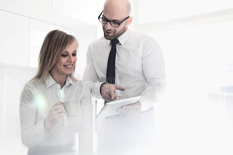 Mi couples adultes heureux d'affaires utilisant la tablette à la maison photographie stock