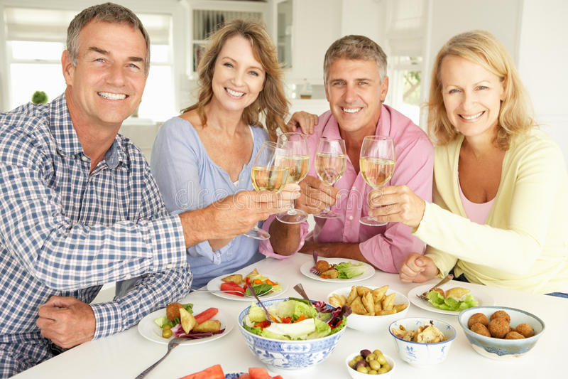Mi couples d'âge à la maison ayant un repas images libres de droits