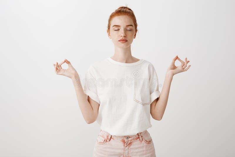 Mi cuerpo es fortaleza Mujer europea joven de moda tranquila con el pelo del jengibre, colocándose con los ojos cerrados y relaja foto de archivo