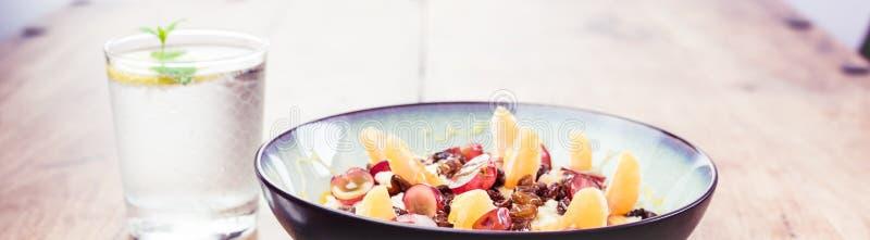 Mi dieta - maneras sanas de soltar el peso - harina de avena sabrosa de la comida con la fruta y un montón de agua imagen de archivo