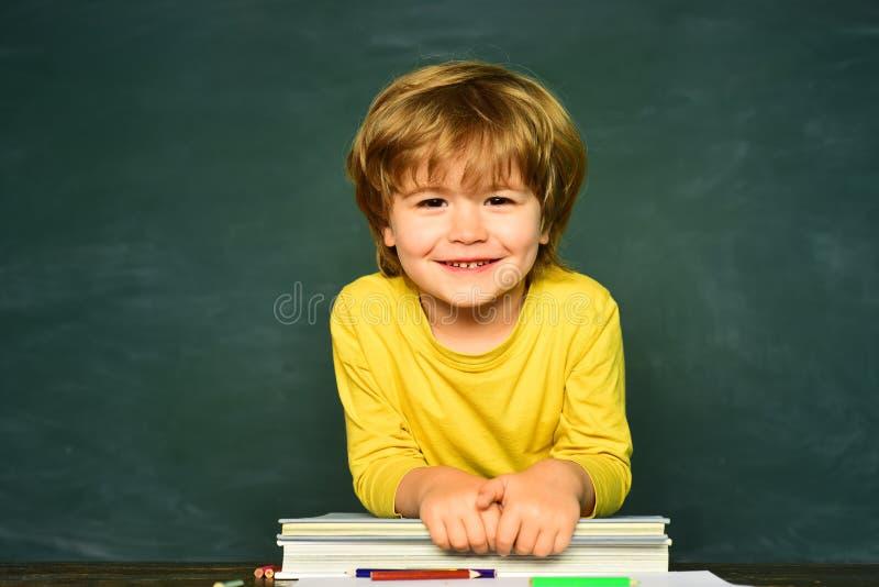 Mi?dos felizes da escola Conceito da escola Sala de aula Rapaz pequeno engra?ado que aponta acima no quadro-negro Crianças da esc foto de stock