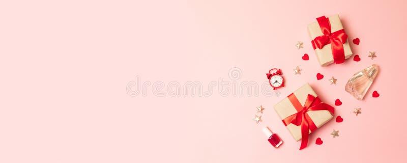 Mi?dzynarodowy kobieta dzie? Pakujący błyszczący czerwony prezenta zbiornik na nowożytnej różowej monochrom desce zdjęcie royalty free