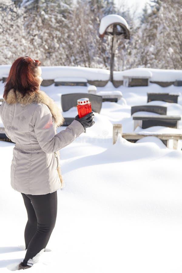 Mi femme âgée avec la bougie sur le cimetière neigeux photo libre de droits