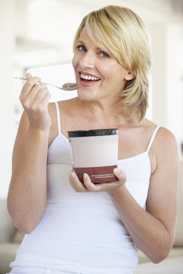 Mi femme adulte mangeant de la glace de chocolat images stock
