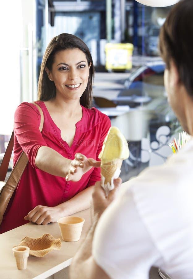 Mi femme adulte recevant la crème glacée du vendeur images stock
