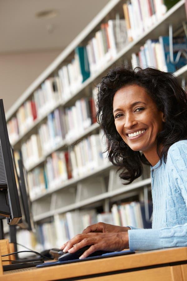 Mi femme d'âge travaillant sur l'ordinateur dans la bibliothèque image libre de droits