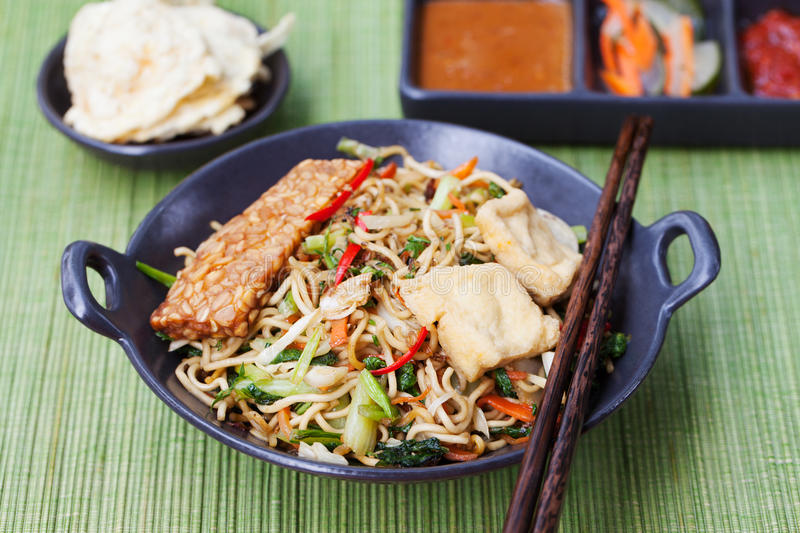 Mi goreng,mee goreng Indonesian cuisine, spicy stir fried noodles with and assortment of asian sauces royalty free stock image