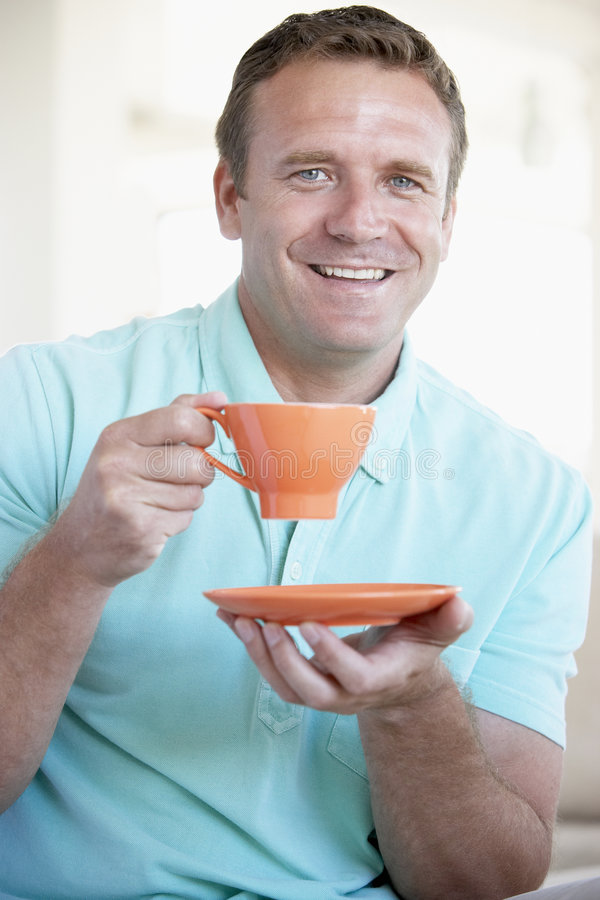 Mi homme adulte retenant la tasse orange et le sourire images libres de droits