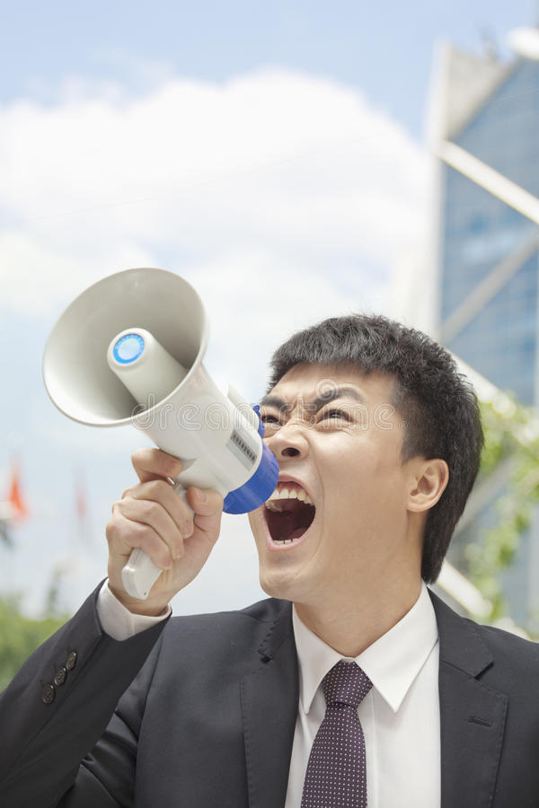Mi homme d'affaires adulte hurlant dans un mégaphone, dehors, Pékin, Chine image stock
