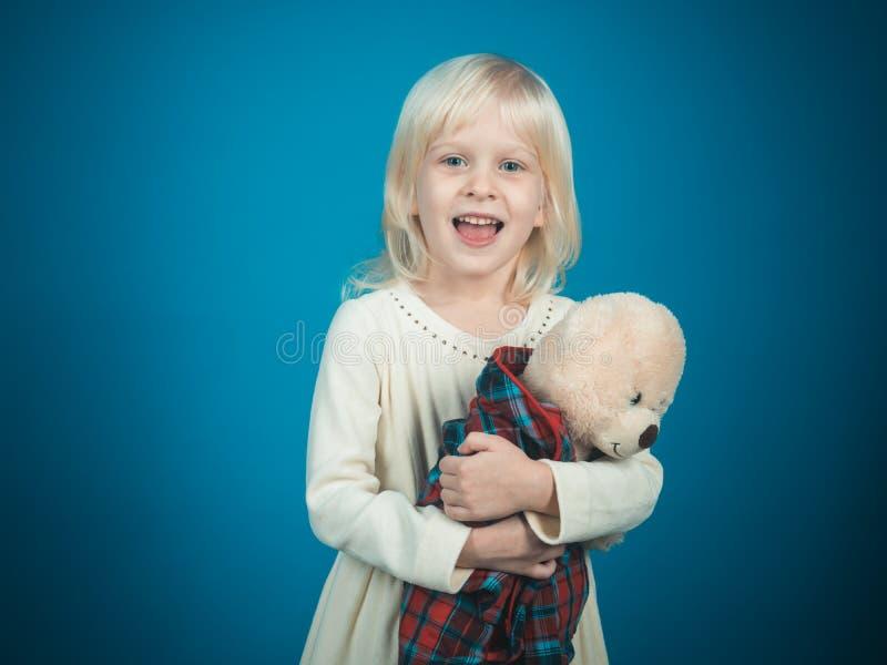 Mi juguete preferido de la niñez Niña con el oso de peluche Pequeño oso del juguete del control de la muchacha Poco niño con el j fotos de archivo libres de regalías