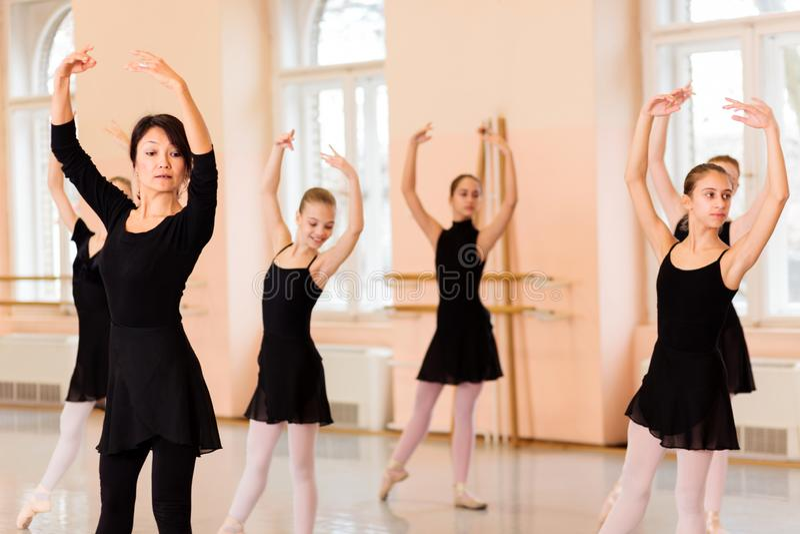 Mi professeur féminin adulte de ballet montrant des mouvements devant un groupe d'adolescentes images libres de droits