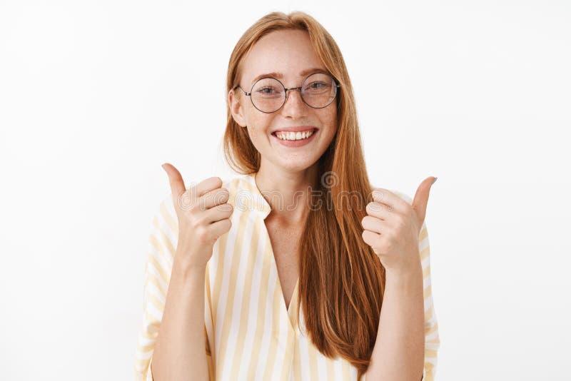 Mi respuesta sí Pelirrojo femenino contento del pelirrojo creativo feliz y entusiasta con las pecas lindas en vidrios y amarillo foto de archivo libre de regalías