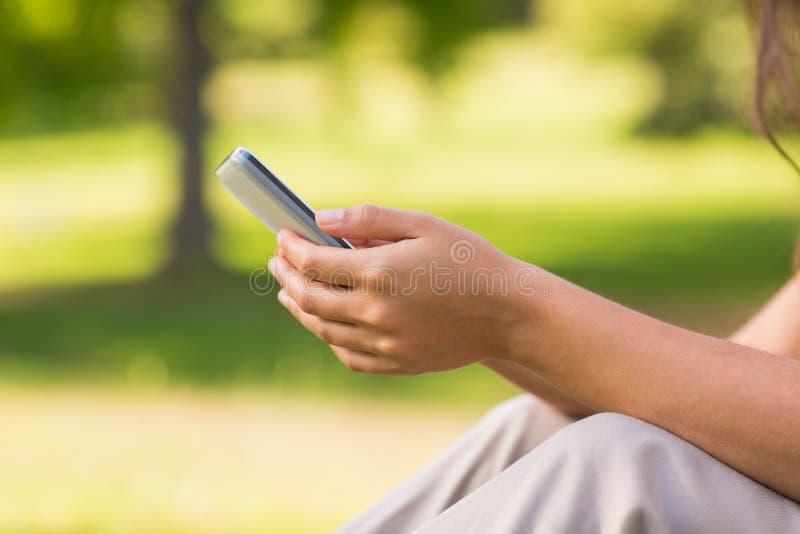 Mi section de la messagerie textuelle de femme en parc photos libres de droits