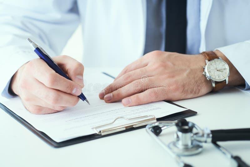 Mi section de la prescription masculine d'écriture de docteur au patient à la table de travail Le docteur enregistre les symptôme photo stock