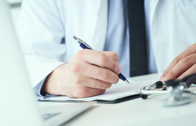 Mi section de la prescription masculine d'écriture de docteur au patient à la table de travail Panacée et économies de la vie, tr image libre de droits