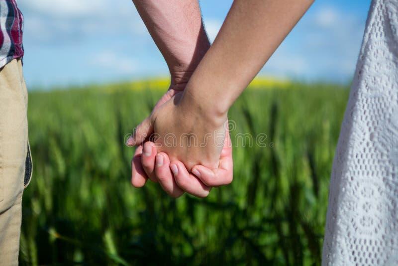 Mi section des couples tenant des mains dans le domaine images stock