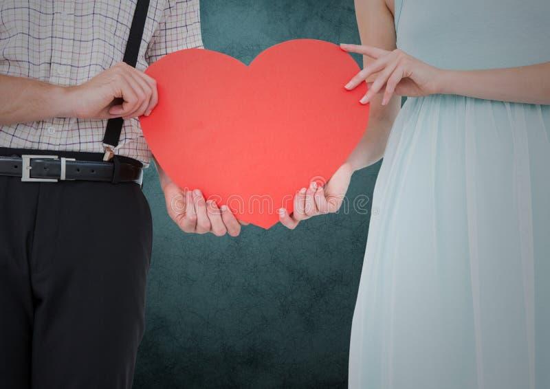 Mi section des couples tenant les coeurs rouges photo stock