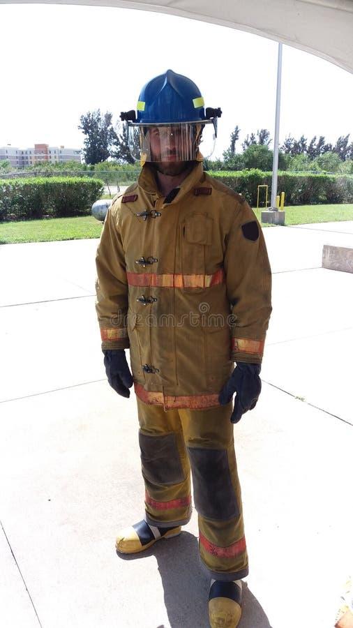 Mi trabajo es extinguir los fuegos En guardia Bombero con el uniforme y el casco Masculinidad y trabajo masculino Deber de hombre fotos de archivo