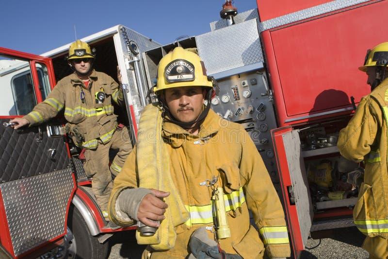 Mi travailleur adulte du feu avec des collègues image libre de droits