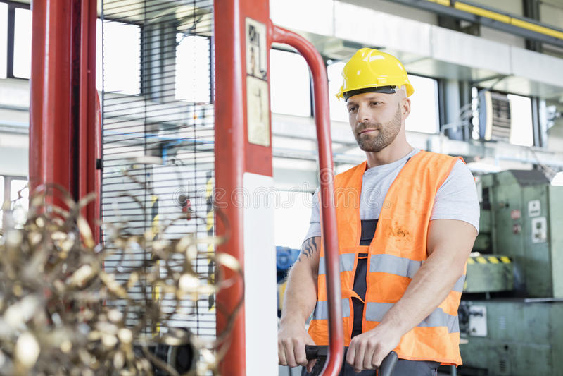 Mi travailleur adulte tirant le camion de main avec les copeaux en acier dans l'usine photo libre de droits
