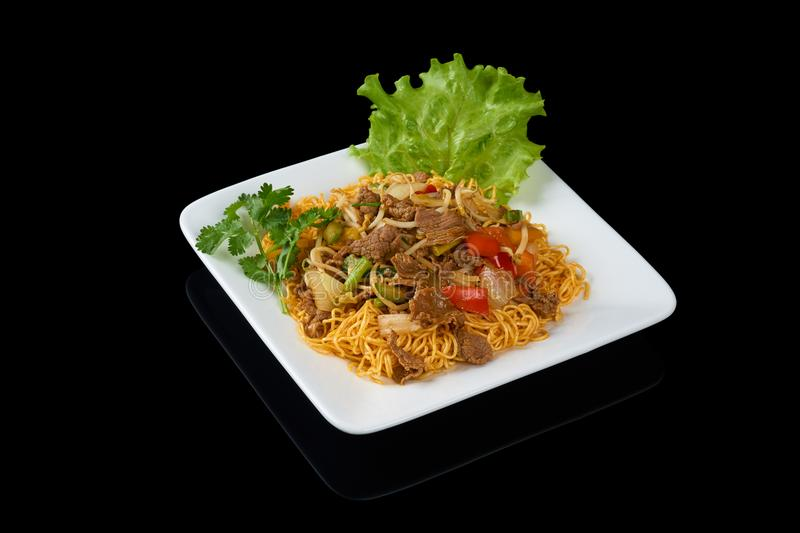 Mi Xao stir-fried noodles. Asian meals on triangle plate isolated on black royalty free stock photography