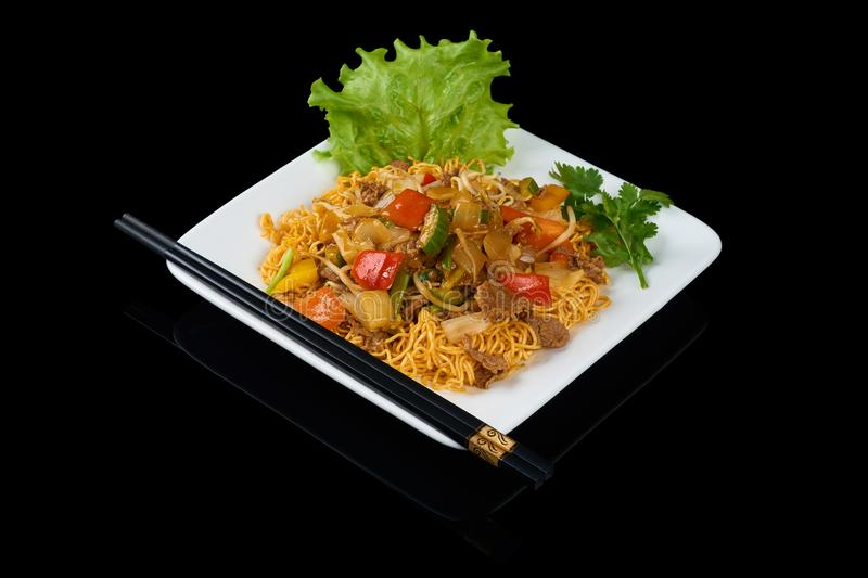 Mi Xao stir-fried noodles. Asian meals on triangle plate isolated on black. Served with chopsticks stock images