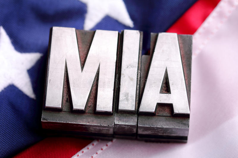 MIA on American Flag. Letterpress blocks forming MIA missing in action letters on Stars and Stripes American flag background. shallow depth of field stock photo