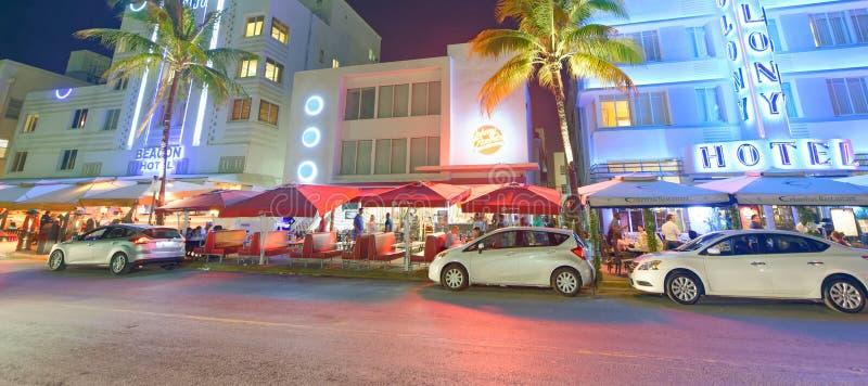 MIAMI BEACH - FEBRUARI 25th, 2016: Bilar och byggnader med ljust kulört neontecken av Art Deco hotell på havdrev i söder arkivfoto
