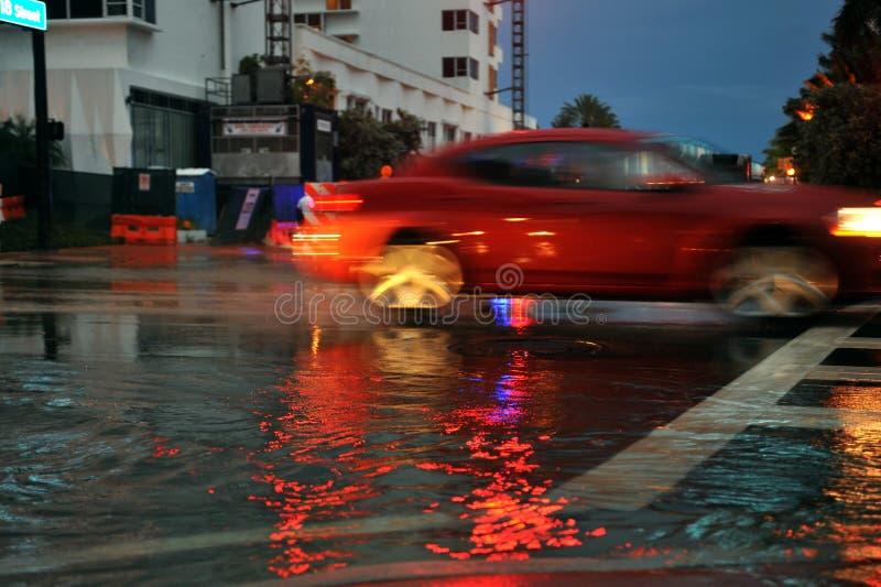 MIAMI BEACH, FL - 18 DE JULHO: Carros que movem ruas e estradas sobre inundadas da praia sul de Miami após chuvas pesadas fotografia de stock royalty free