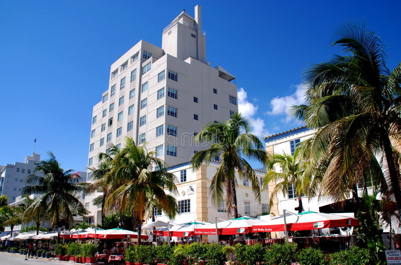 Miami Beach, FL: Ocean Drive Cafés & Hotels. The Tides Hotel, outdoor cafés shaded by umbrellas, and a row of graceful palm trees on Ocean Drive in Miami stock images