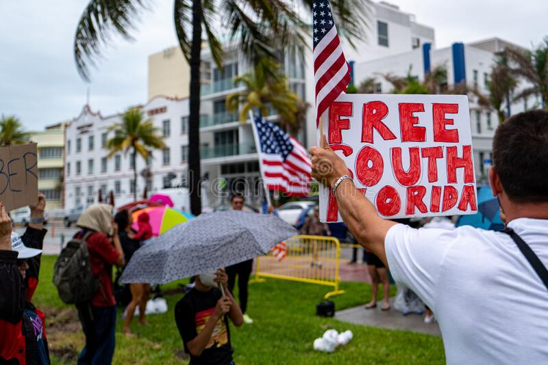 Miami Beach, Florida, USA - May 10, 2020: Free South Florida sign and US flag. Protestors in Lummus Park in Miami Beach. Demanding to the city reopen beaches stock image