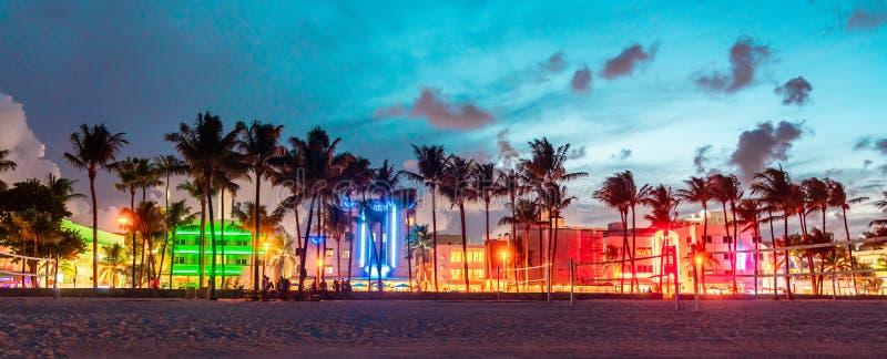 Miami Beach Ocean Drive panorama med hotell och restauranger vid solnedgången Stadskylin med palmträd nattetid Art deco royaltyfri foto