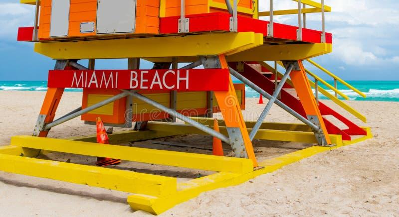 Miami Beach som ?r skriftligt p? ett f?rgrikt livr?ddaretorn royaltyfria foton