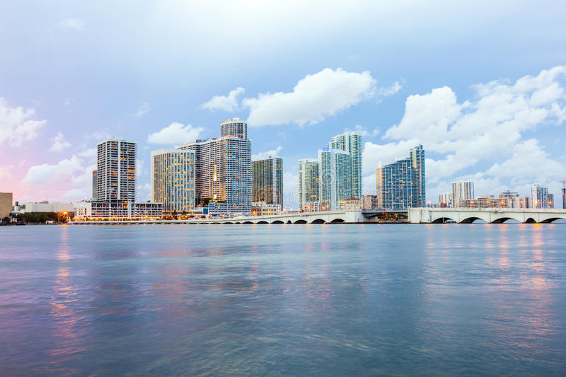 Miami city skyline. Panorama at dusk with urban skyscrapers and bridge over sea with reflection royalty free stock photos