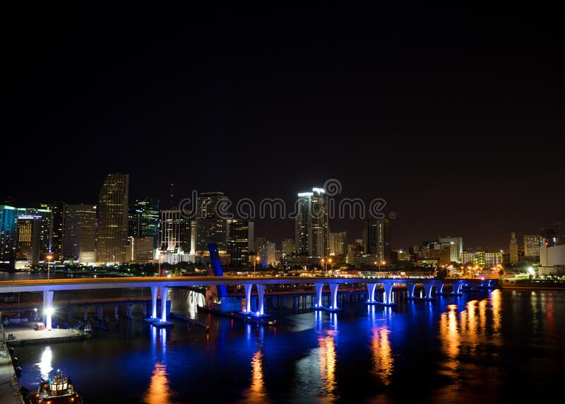 Miami city skyline panorama at dusk with urban skyscrapers and bridge over sea with reflection.  stock photography