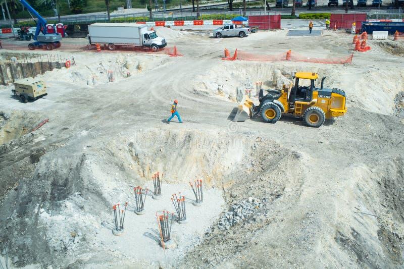 Miami, de V.S. - 30 Oktober, 2015: arbeiders en machines op bouwkuil De bouwterreinwerken aangaande zonnige openlucht Bouw en B royalty-vrije stock afbeelding
