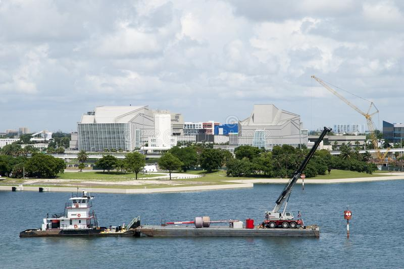 Miami Industrial Platform. The view of a tugboat and drifting platform with a crane in Miami downtown Florida royalty free stock images