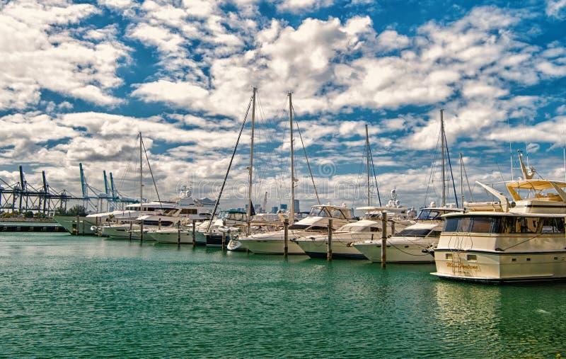 Miami, los E.E.U.U. - 19 de febrero de 2016: yates y barcos de vela en puerto marítimo en el cielo azul nublado El navegar y nave foto de archivo